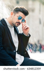 Cool and handsome fashion young man with sunglasses. Stylish man in the city. Outdoors.