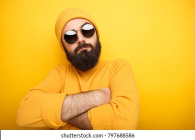Cool handsome man in yellow clothes and sunglasses posing with arms crossed.