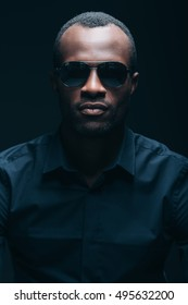 Cool and handsome. Portrait of handsome young African man in sunglasses looking at camera while being in front of black background