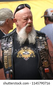 Cool Harley-Davidson biker with long moustache and sunglasses on forehead on yellow background at the St Tropez rally  Port Grimaud, Provence/france  May 10 - 2014