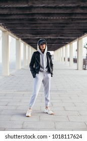 Cool and hip young female in grey fashionable tracksuit, sweatpants and hoodie poses for camera during fashion photoshoot, urban street style for social media or fashion outfit blog