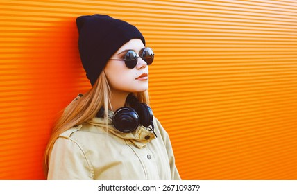 Cool hipster girl wearing a black hat and headphones listens to music enjoys freedom against a colorful wall in the city, street fashion concept