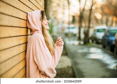 cool hipster young girl in pink hoodie standing against a wooden wall on the street enjoying youth and smiling, dreaming about something good