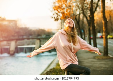 cool hipster young girl in pink hoodie standing by a river in the city enjoying the sun of autum or springtime
