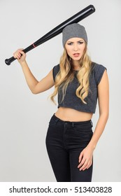 Cool hot fashionable woman bandit dressed in hat with baseball bat on white background in studio