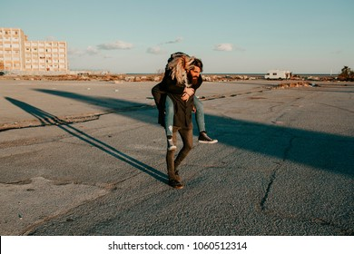 Cool indie couple having fun outdoors while he gives her a piggyback on an abandoned place.