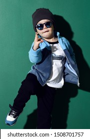 Cool kid boy in blue sunglasses, headwear, fleece jacket, white t-shirt with muscle car print, pants and sneakers is dancing, jumping, showing cool sing on green
