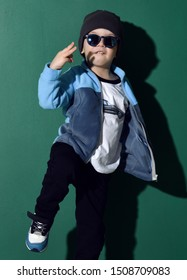 Cool kid boy in blue sunglasses, headwear, fleece jacket, white t-shirt with muscle car print, pants and sneakers is dancing, acting like a hip-hop star, showing cool sing on green