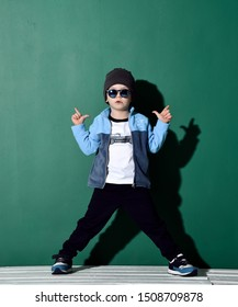 Cool kid boy in blue sunglasses, headwear, fleece jacket, white t-shirt with muscle car print, pants and sneakers is posing like a gangster with two finger guns on green