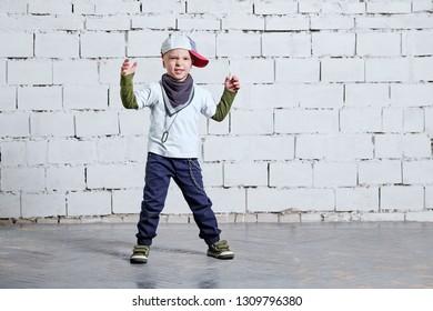 Cool kid boy dancing break dance.Hip-hop style. studio, brick wall background. Little rapper chiild man wears a cap, sneakers, pants, t-shirt, street style clothes.