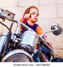 Cool little biker girl playing and having fun on fashioned motorcycle. Humorous portrait of child points to the road with finger.
