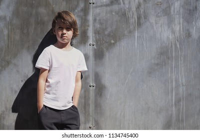 Cool little boy wearing a white blank t-shirt and black jeans standing on concrete wall background. Horizontal mock up.