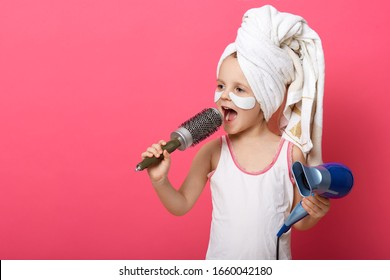 Cool little girl with hair dryer in hands. Portrait of beautiful female child singing with hair comb in hand isoalted on rosy background, charming little kid having fun in batroom after taking shower.