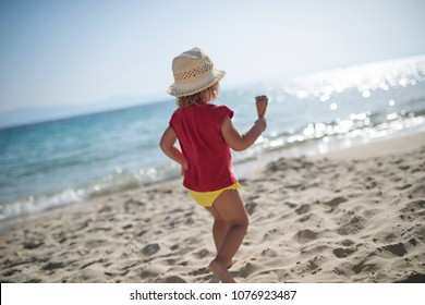 Cool little girl with icecream running on summer holiday