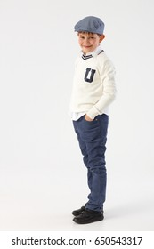 Cool little schoolboy standing with hands in pockets, wearing hat.