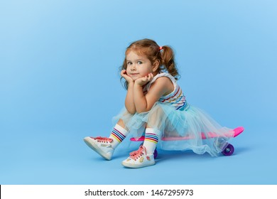 Cool little toddler girl in bright clothes sits on a skateboard and looking at the camera isolated on blue background
