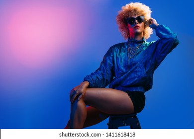 Cool lookig young black woman with afro style hair in colored background sitting on a bench wearing sunglasses
