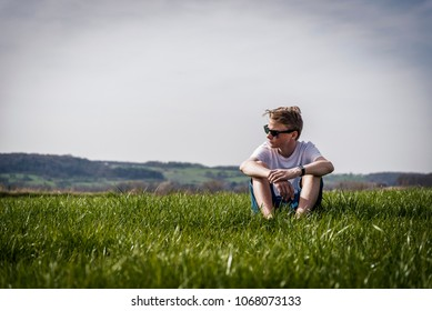 cool looking boy sitting relax in a field