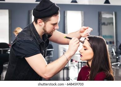 cool male make-up artist doing brunette girl in a dress make-up in beauty salon