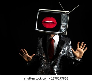 cool male performer with a television as a head. the tv sexy lips on the screen and the man is dancing