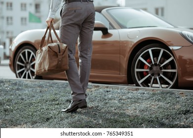 Cool man beautiful model outdoors, city style fashion. A handsome man model walking in the city center next to some cars. urban setting. The young boy as trendy, modern clothing with bag