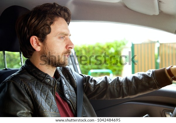 Cool man with blue eyes driving car