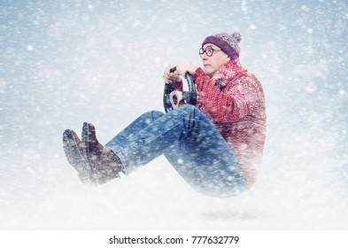 Cool man driver in round glasses, red sweater, and hat, with steering wheel. Winter, snow, blizzard