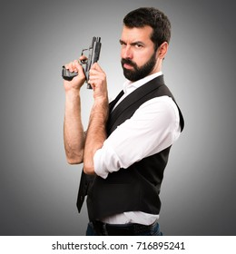 Cool man holding a pistol on grey background