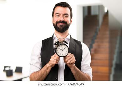 Cool man holding vintage clock inside house