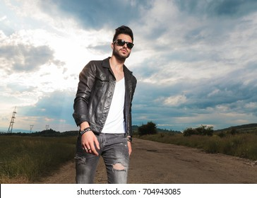 cool man in leather jacket walking on a country road