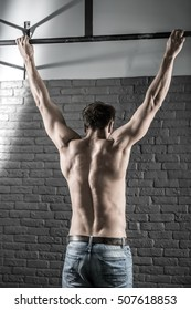 Cool man with a naked torso hangs on the crossbar in the gym on the gray brick wall background. He wears blue jeans. Shoot from the back. Vertical.