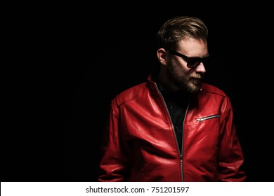 Cool man in a red leather jacket with sunglasses standing against a black background.