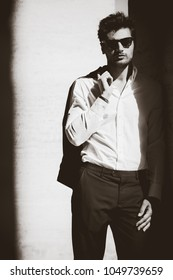 Cool man with sunglasses and white shirt. In twilight leaning against the wall. Black and white with shades.