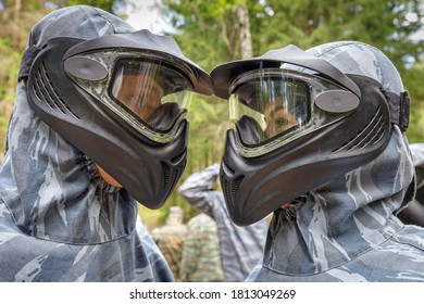 Cool man and woman in paintball masks look at each other