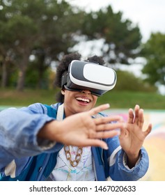 Cool millennial black woman with virtual reality glasses, on a skateboard in an outdoor skate park