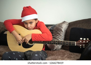 Cool mixed boy Matiss playing on guitar and singing a Christmas song. Boy in Santa Claus hat singing at his house on Happy New Year. Childrens hobby. Boy learning how to play guitar.