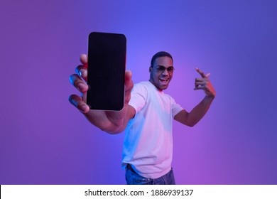Cool Mobile Offer. Excited African Guy Demonstrating Smartphone With Black Screen, Standing Under Neon Lighting, Joyful Millennial Man Showing Free Mockup Copy Space For Your App Or Website Design