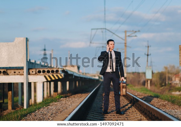 A cool and modern male businessman in a suit with a suitcase is walking along the paths from the train and talking on the phone. Business walk and serious conversation. Late for the train.