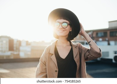 Cool and modern young beautiful teenager or woman poses to camera in sunset light on rooftop of building, wears reflective glasses with lenses, smiles and laughs happy and satisfied with lifestyle