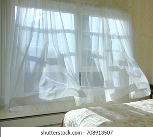 Cool ocean breeze blowing the bedroom curtains
