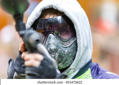Cool paintball player with marker aiming in camera. Closeup.