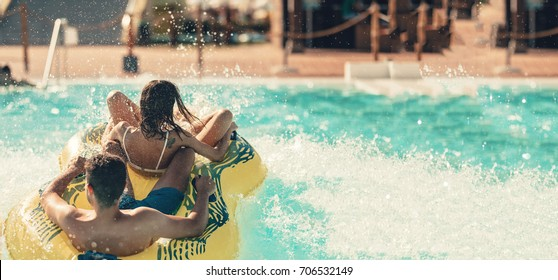 Cool people having fun on the water slide with friends in the aqua fun park glides playing happy and water splashes are all over. Blue sky background looks amazing sunlight. copy space for text