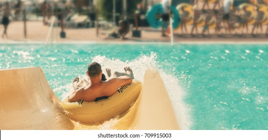 Cool people having fun on the water slide with friends and familiy in the aqua fun park glides playing happy and water splashes are all over. Blue sky background looks amazing sunlight