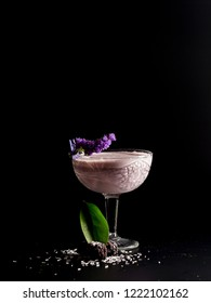 Cool pink blueberry cocktail with lilac flowers. Restaurant serve, on a black background.