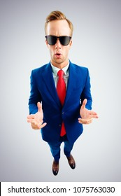 I am cool! Portrait of funny young businessman in sunglasses, blue suit and red tie, top angle view shot, over grey background. Business concept.