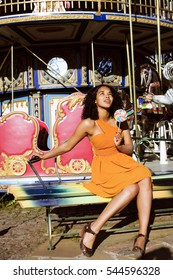 cool real african american teenage girl with candy near carousels at amusement park, lifestyle people concept