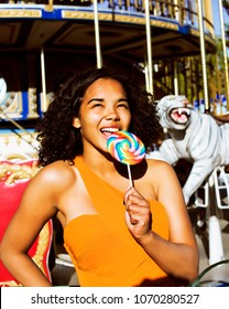 cool real modern teenage girl with candy near carousels at amusement park