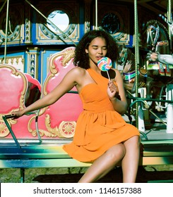 cool real modern teenage girl with candy near carousels