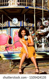 cool real teenage girl with candy near carousels at amusement pa