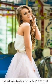 cool real teenage girl near carousels at amusement park walking